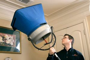 Vallus energy consultant tests airflow from ceiling vent